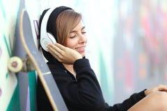 Het meisje die van de schaatsertiener aan de muziek met hoofdtelefoons luisteren Stock Afbeelding
