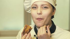 Het meisje die van de tienerkok een cakeslowmo eten stock footage