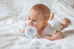 Het meisje die van de zuigelingsbaby op het witte bed met speciale fles water met uitsteeksel liggen Probeert om aan haar te knag stock afbeeldingen