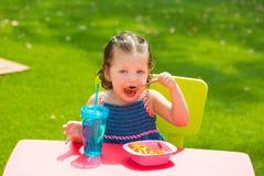 Het meisje die van het peuterjonge geitje de deegwaren van de macaronitomaat eten Stock Fotografie