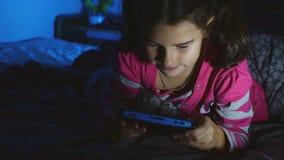 Het meisje die van het tienerjonge geitje een draagbare videospelletjeconsole binnen spelen bij nacht stock footage