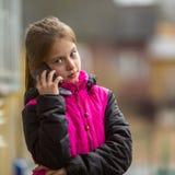 Het meisje die van tien jaar op mobiel in openlucht spreken Mededeling Stock Afbeelding