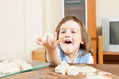 Het meisje die van twee jaar van plasticine of deeg in huis beeldhouwen Stock Afbeelding