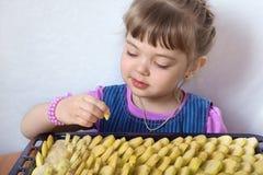 Het meisje die van vier jaar appeltaart voorbereiden Stock Foto's