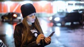 Het meisje die vinger op het schermsmartphone richten op achtergrondverlichting bokeh kleurt licht in nacht atmosferische stad stock footage