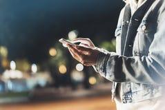 Het meisje die vinger op het schermsmartphone richten op achtergrondverlichting bokeh kleurt licht in nacht atmosferische stad, h royalty-vrije stock afbeelding
