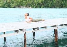 Het meisje die yoga uitoefenen stelt cobra op pier door overzees royalty-vrije stock foto's