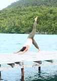 Het meisje die yoga uitoefenen stelt three-legged benedenwaartse hond op pier door overzees stock foto's