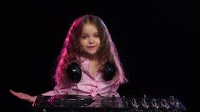 Het meisje DJ in roze overhemd verspreidt luchtkussen stock footage