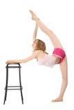 Het meisje doet gymnastiek, die voor kruk houdt Royalty-vrije Stock Foto's