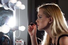 Het meisje doet make-up Royalty-vrije Stock Afbeeldingen