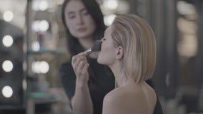 Het meisje doet make-up door de spiegel stock footage