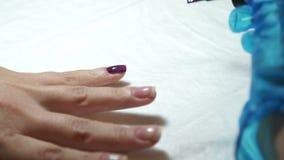 Het meisje doet manicure De vrouw schildert vingernagels stock footage