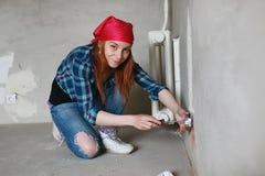 Het meisje doet reparaties in de flat Huis die tot een nieuwe flat leiden De arbeider maakt gepleisterde reparaties, en stock foto's