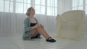 Het meisje doet zich het uitrekken en het opwarmen in opleiding in een heldere ruimte met groot vensters en Tulle stock footage
