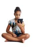 Het meisje, donker-gevilde tiener bekijkt het scherm van de tablet Stock Foto's