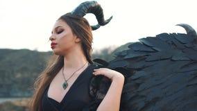 Het meisje in donkere uitstekende kleding met reusachtige zware sterke vleugels achter achter haar verwijdert haar lang haar uit  stock videobeelden