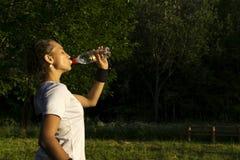 Het meisje dooft haar dorst in openlucht na het spelen sporten stock foto's