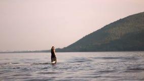 Het meisje door de rivier in een zwarte kleding komt in het water op de achtergrond van bergen stock video