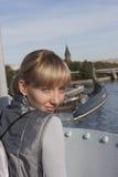 Het meisje door het schip tegen de stad Stock Foto's