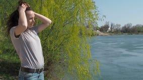 Het meisje is door het water Jonge vrouw in de verse lucht door de rivier De wind ontwikkelt het haar stock videobeelden