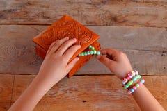 Het meisje draagt armbanden De kinderenhanden nemen armband in houten doos Oude houten achtergrond Royalty-vrije Stock Fotografie