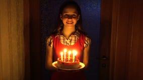 Het meisje draagt de verjaardagscake met kaarsen van de duisternis stock videobeelden