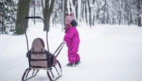 Het meisje draagt een slee in het Park, een onafhankelijk kind stock foto's