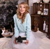 Het meisje draagt gebreide cardigan en fatinrok, die naast Kerstboom stellen royalty-vrije stock afbeelding