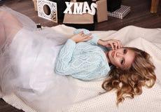 Het meisje draagt gebreide cardigan en fatinrok, die naast Kerstboom stellen stock fotografie