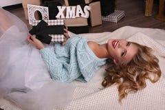 Het meisje draagt gebreide cardigan en fatinrok, die naast Kerstboom stellen royalty-vrije stock fotografie