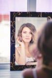 Het meisje draagt oorringen van spiegels. Stock Afbeeldingen