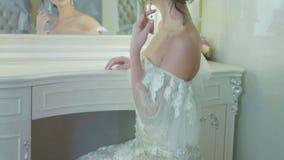 Het meisje draagt oorringen voor een spiegel bij luxebinnenland in langzame motie stock video