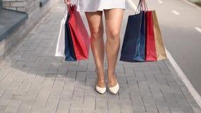 Het meisje draagt pakketten met het winkelen in handen na het winkelen Langzame Motie stock video