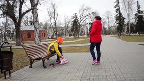 Het meisje draagt rolschaatsen op parkbank, familievakantie in het park stock videobeelden