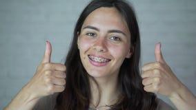 Het meisje draagt steunen op haar tanden ongemak, pijn stock video