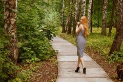 Het meisje draaide rond het lopen langs de weg in het Park Royalty-vrije Stock Fotografie