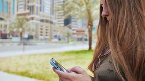 Het meisje draait een aantal of een bericht op smartphone tegen de achtergrond van de stadsstraten van Doubai stock afbeelding