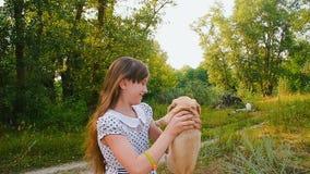 Het meisje draait een puppy op handen stock video