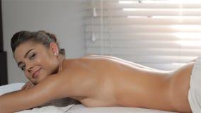 Het meisje draait haar gezicht op massagelijst stock video