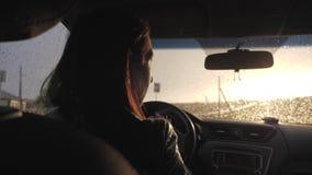 Het meisje dreef terwijl de regen viel Drijven op de weg bij zware regens zou voorzichtig moeten zijn Zware regens  stock videobeelden