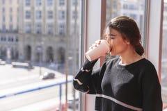 Het meisje drinkt koffie en bevindt zich door panoramisch venster stock fotografie