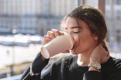 Het meisje drinkt koffie en bevindt zich door panoramisch venster stock afbeeldingen