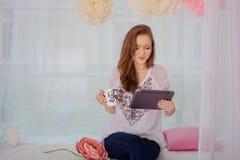 Het meisje drinkt koffie met de tablet Het concept Internet Royalty-vrije Stock Afbeelding