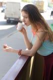 Het meisje drinkt koffie op een balkon dichtbij de weg royalty-vrije stock foto's