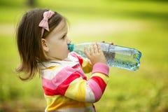 Het meisje drinkt mineraalwater Stock Afbeeldingen