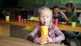 Het meisje drinkt sap op de achtergrond van zijn moeder en grootmoeder stock footage