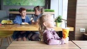 Het meisje drinkt sap op de achtergrond van zijn moeder en grootmoeder stock video
