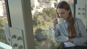 Het meisje drinkt thee door het venster van in restaurant stock videobeelden