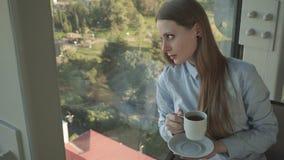 Het meisje drinkt thee door het venster van in restaurant stock video